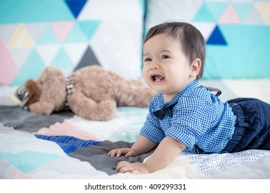 Cute 11 month old mixed race Asian Caucasian baby boy dressed up with braces and bow tie plays happily on a colourful geometric shaped bed cover with his brown teddy bear