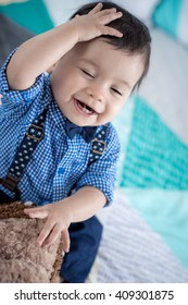 Cute 11 month old mixed race Asian Caucasian boy dressed in braces and bow tie plays cheerfully with his brown teddy bear on a colourful geometrically shaped bed cover