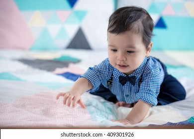 Cute 11 month old mixed race Asian Caucasian boy dressed in braces and bow tie plays cheerfully on a colourful geometrically shaped bed cover