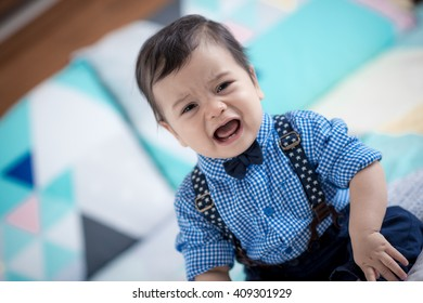 Cute 11 month old mixed race Asian Caucasian boy dressed in braces and bow tie cries sadly on a colourful geometrically shaped bed cover