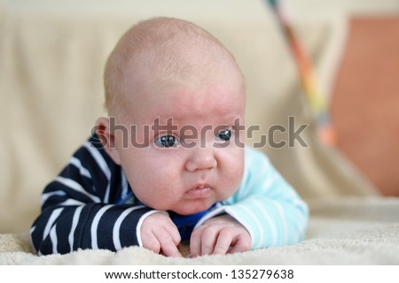 Cute 1,5 month old Caucasian baby boy with short blonde hair wearing a  bright