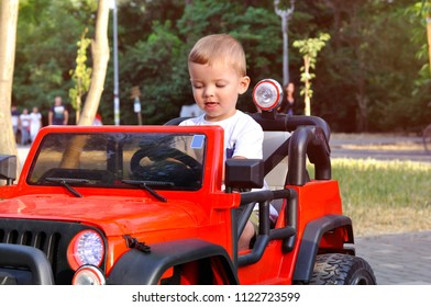 Cute 2 year old boy in a white T shirt is riding a red electric car in the park