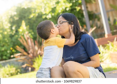 Cute 2 year old mixed race boy kisses his asian mother outside in their backyard