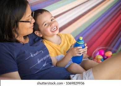 Cute 2 year old mixed race asian caucasian boy drinks water from a water bottle while playing with his mother on a colorful hammock