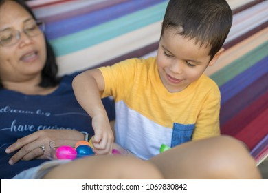 Cute 2 year old mixed race asian caucasian boy picks candy from colorful eggs while sitting with his mother on a colorful hammock