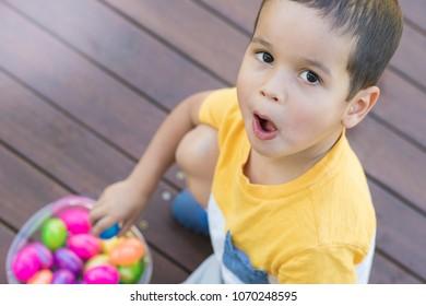 Cute 2 year old mixed race asian caucasian boy chews candy on a wooden garden deck