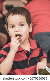 Cute 2 year old mixed race Asian Caucasian boy eats chips at a sporting event
