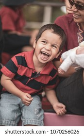Cute 2 year old mixed race asian caucasian boy laughing and playing with his mom and doll sitting at a sporting event