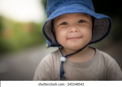Cute 2 year old mixed race Asian Caucasian boy wearing a blue hat outside smiles sweetly looking at the camera
