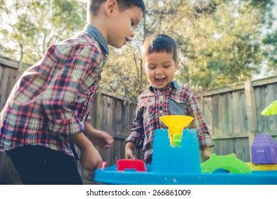 Cute 2 year old mixed race Asian Caucasian brothers play happily with a water toy in their suburban house backyard. Filtered effects