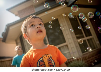 Cute 2 year old mixed race Asian Caucasian boy plays happily with bubbles in his family home backyard