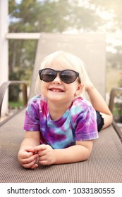A cute, 2 year old toddler child is smiling as she poses for the camera on a beach chair under the creen by the pool on a summer day.