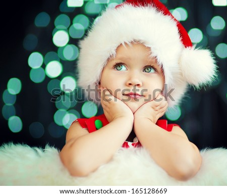 605e25e68113e A cute 2-years old girl in a Santa hat sitting and propping her cheek with  the hands and dreaming about Santa Claus against Christmas glitter close-up  - ...