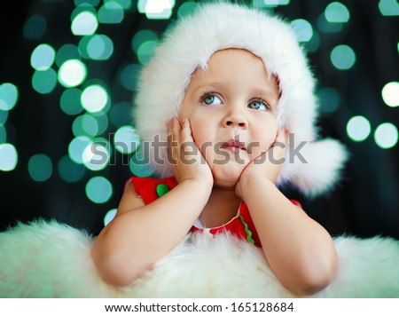 fcfc63a966661 A cute 2-years old girl in a Santa hat sitting and propping her cheek