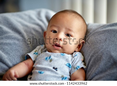 Cute 3 month old baby boy looking at camera with shallow depth of field