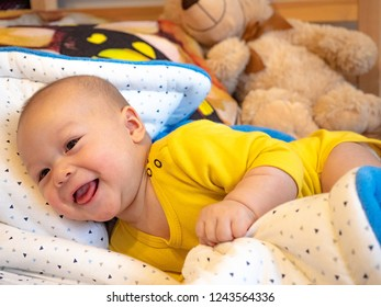 Cute 3 months old old mixed race Asian Caucasian boy looking happy smiling and laughing at the camera, tummy time on belly on the bed, healthy child baby boy. Half Thai half Polish.
