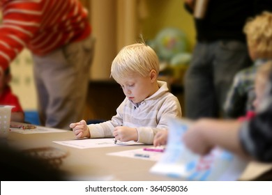 A cute 3 year old boy child is sitting quietly in Pre-K Sunday School class, coloring a picture, as teachers walk around behind him.