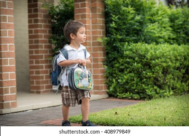 Cute 3 year old mixed race Asian Caucasian boy confidently leaves home for his first day at preschool