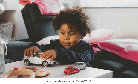 Cute 3 years old African American kid playing with toy cars at home