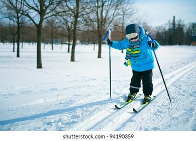Cute 3 years old boy skiing on cross