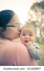 Cute 4 month old mixed race Asian Caucasian Thai baby snuggles with his Thai Asian mother outdoors in the late afternoon sun in Australia. Filtered color shift, sun flare, and soft focus effects