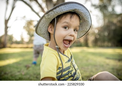 Cute 4 year old mixed race Asian Caucasian boy wearing a hat and playing outside in the summer sun