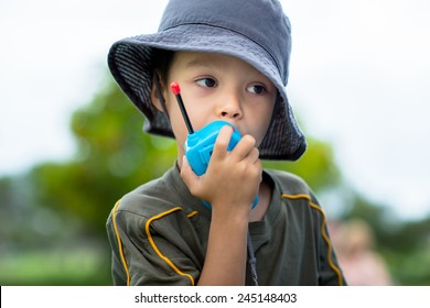 Cute 4 year old mixed race Asian Caucasian boy plays outside in a playground with a toy walkie talkie radio