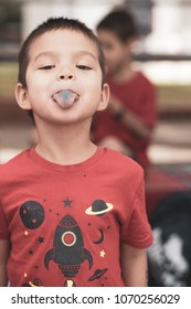 Cute 5 year old mixed race boy pokes his blue tongue out after eating blue candy