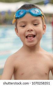 Cute 5 year old mixed race asian caucasian boy wearing blue goggles at an outdoor pool