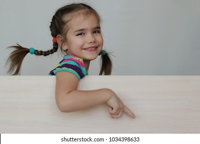 Cute 5 years old girl with funny pigtails pointing with her fingers right down corner on white board, space for copy, advertising and announcement concept, studio shot over white background