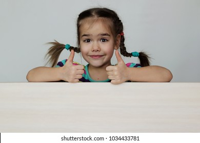Cute 5 years old girl with funny pigtails showing like gesture with thumb up on white board, space for copy, advertising and announcement concept, studio shot over white background