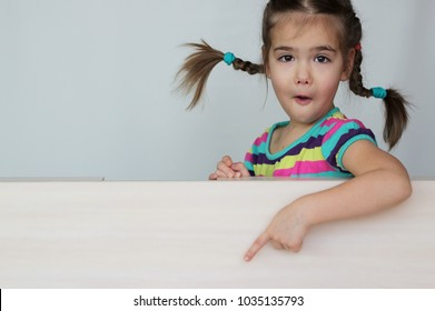 Cute 5 years old girl with funny pigtails pointing with her fingers left down corner on white board, space for copy, advertising and announcement concept, studio shot over white background