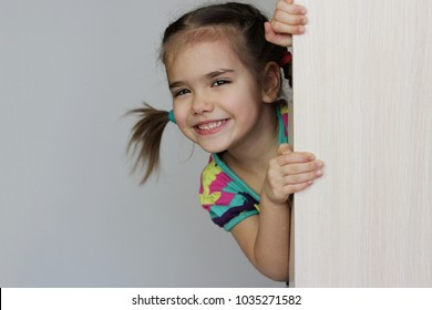 Cute 5 years old girl with funny pigtails peeping out through the blank wall over white background, space for copy, advertising and announcement concept, studio shot