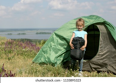Cute 5 years old girl holding a sleeping bag near the tent over beautiful landscape, she is ready to overnight stop, active lifestyle, family recreational weekend, summer outdoor