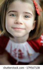 Cute 5 years old girl look straight at you and smiles, dressed in a traditional Romanian dress