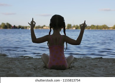Cute 5-6 year girl meditating on the beach, relax and self-development concept, sport and recreational, summer outdoor