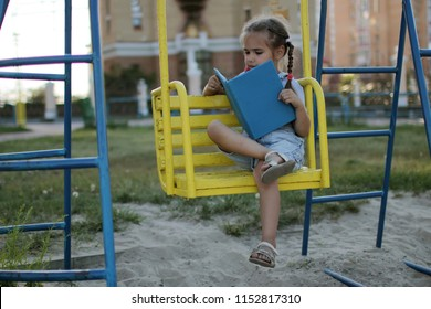 Cute 5-6 year girl reading a book on the playground, education and self-development concept, book lover, summer outdoor