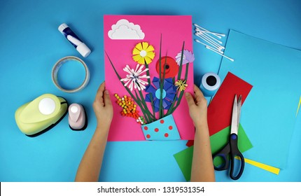 Cute 5-6 years old girl making spring DIY flowers with colored paper for her mom in Mothers Day, decorative punchers to create fun and easy with children, concept for kindergarten, top view image