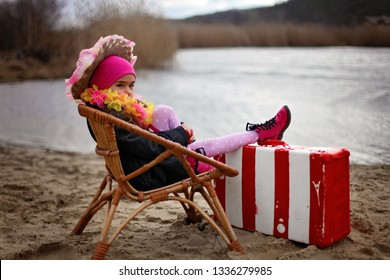 Cute 5-6 years old girl in a coat and flowers garland sitting on a beach enjoying the beautiful view, outdoor, ready for summer, holiday and travel concept
