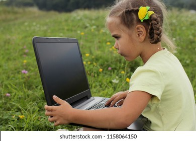 Cute 5-6 years old little girl sharing a photo on social media in internet in the mountains among beautiful nature, summer outdoor, social network, gadget and technology concept
