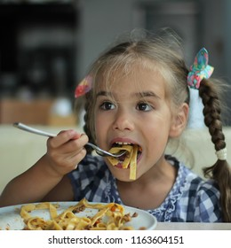 Cute 5-6 years old little girl eating pasta with tomato sauce sitting in the road cafe during her voyage, food and drink