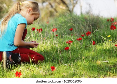 Cute 7 years old girl sitting in the spring green meadow