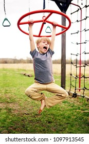A cute 8 year old child is screaming as he plays and spins around on his backyard playground equipment.