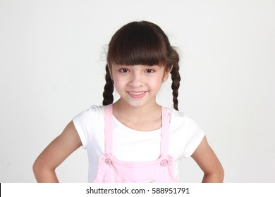 Cute 8 year old girl with pigtails smiling.  Close up of face.  Mixed race Thai Caucasian. Wearing a white shirt and pink overalls.