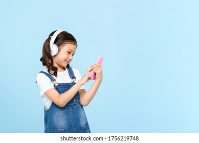 Cute 8 year-old girl wearing headphones listening to music online from mobile phone isolated on light blue background