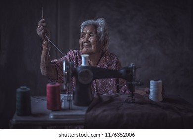 Cute 90 year old senior woman using vintage sewing machine. adorable elderly woman sewing clothes in her old family home.