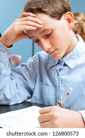 Cute adolescent school boy concentrates while taking a standardized test.