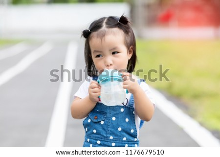 Cute adorable 1-2 year old baby girl holding nursing bottle and drinking  formula milk