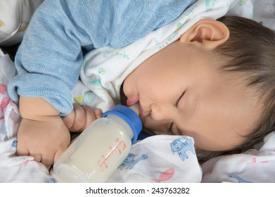 Cute and  adorable Asian baby sleeping   drinking milk from the bottle alone on the bed