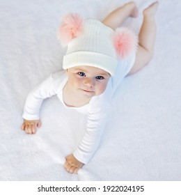 Cute adorable baby child with warm white and pink hat with cute bobbles. Happy baby girl learning crawl and looking at the camera. Close-up for xmas holiday and family concept
